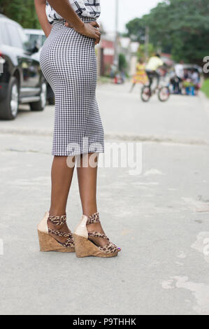 Image of beautiful legs of a young woman standing posing in the street - Stock Image