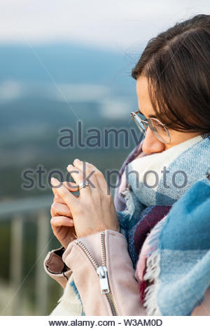 Closeup shot of a beautiful woman with scarf showing her engagement ring blurred background - Stock Image