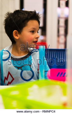 Poznan, Poland - February 2, 2019: Young boy sitting in front of a tube with blue liquid used for a experiment during a workshop in a university. - Stock Image