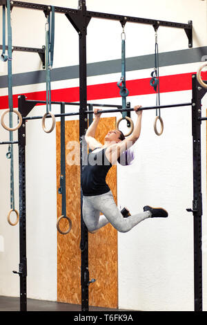 Fit young woman athlete doing pull-ups on rings while exercising in a gym during her workout to strengthen her upper body muscles - Stock Image