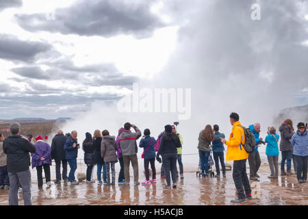 Geysir, Iceland: Group of tourists looking at geyser - Stock Image