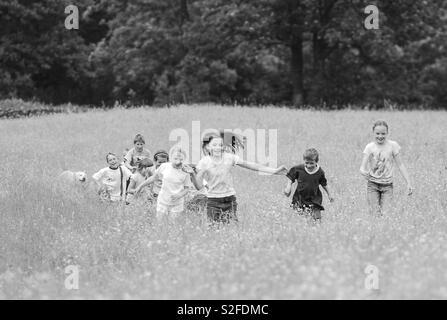 Running children in meadow - Stock Image