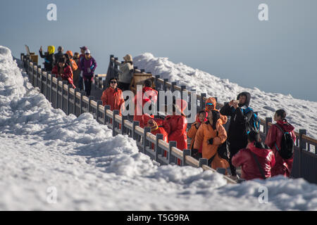 Lijiang, China's Yunnan Province. 21st Apr, 2019. Tourists visit the Yulong Snow Mountain in Lijiang City, southwest China's Yunnan Province, April 21, 2019. According to local authority, tourism started to heat up when a faster train service was launched between Lijiang and provincial capital Kunming in early 2019. During the first season, Lijiang welcomed 12.325 million arrivals and saw a total revenue of 25.637 billion yuan, up 21.5 percent and 15.13 percent respectively than the previous year. Credit: Hu Chao/Xinhua/Alamy Live News - Stock Image