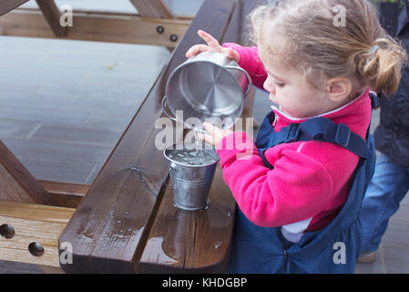 Little girl pouring water from one pail to another - Stock Image