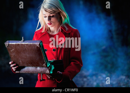 Woman examining contents of suitcase - Stock Image