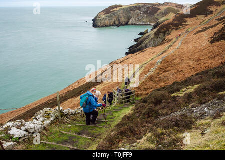 Walkers hiking down steps on Wales coast path coastal footpath towards Porth Llanlleiana from Cemaes, Isle of Anglesey, Wales, UK, Britain - Stock Image
