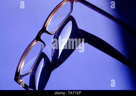 shadow of glasses on purple background - Stock Image