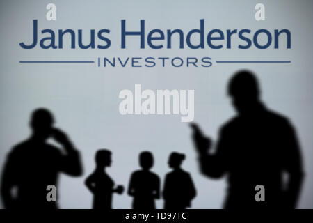 The Janus Henderson Investors logo is seen on an LED screen in the background while a silhouetted person uses a smartphone (Editorial use only) - Stock Image