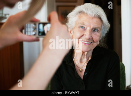 Woman taking photos with camera phone - Stock Image