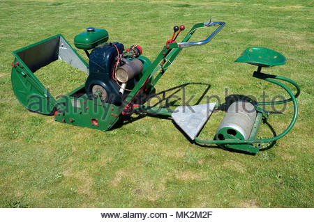 A vintage petrol engine 24 inch cutter Dennis lawn mower, with ride on seat/roller attachment fitted. - Stock Image