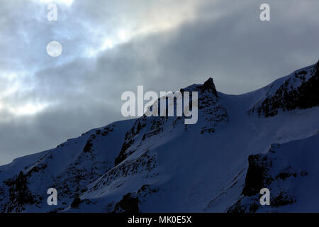 Round Sun in Cloudy Sky, over a Snowy Ridge. Svalbard, Norway - Stock Image