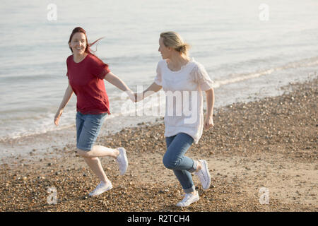 Playful lesbian couple holding hands and running on sunny beach - Stock Image