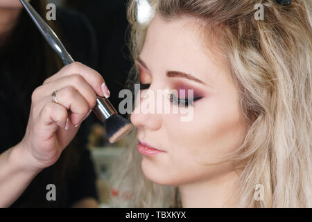 Make-up artist working in make-up studio, applying makeup on face of female clients. Makeup artist applies highlighter with makeup brush. Evening make - Stock Image