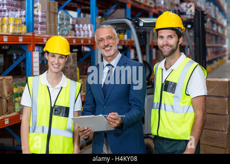 Portrait of wrehouse manager and co-workers standing with clipboard - Stock Image