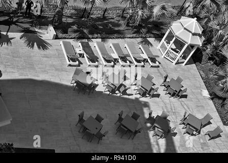 Hotel outdoor lounge area with gazebo and table and chairs seating. Black and white photography - Stock Image