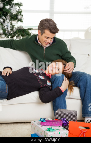 Couple With Christmas Gifts On Floor Relaxing On Sofa - Stock Image
