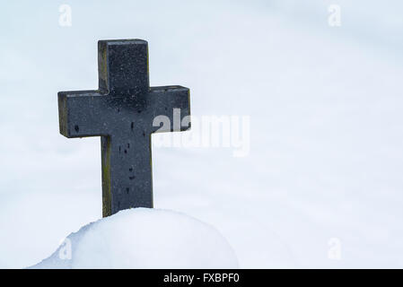 Closeup of black stone cross in cemetery and snow - Stock Image