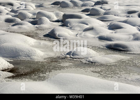 Abstract composition showing dunes of snow on frozen water landscape - Stock Image