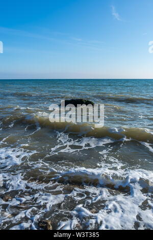 Lonely stone in the sea at the coast - Stock Image