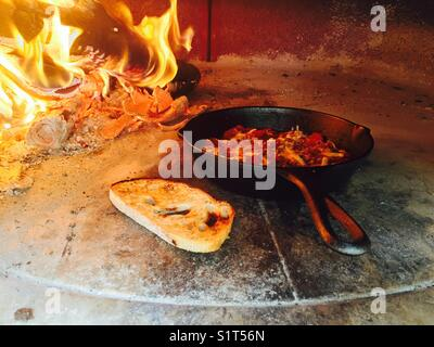 Wood fire cooking tomatoes and toast - Stock Image