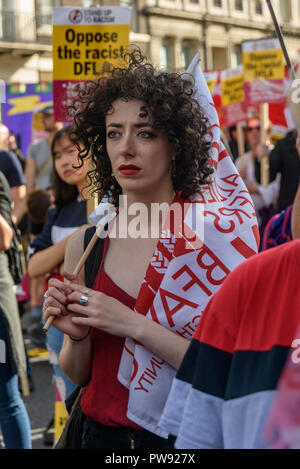 London, UK. 13th October 2018.   A woman in the crowd with a Baker's Union (BFAWU) flag at the rally in London to oppose racism  and fascism close to where the racist, Islamophobic DFLA were ending their march on Whitehall bringing together various groups to stand in solidarity with the communities the DFLA attacks. The event was organised by Stand Up To Racism and Unite Against Fascism. Peter Marshall/Alamy Live News - Stock Image