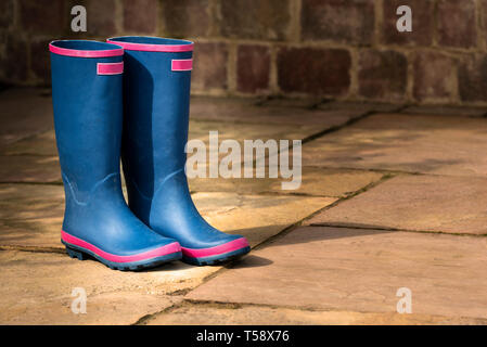 Pair of blue wellington boots on a stone patio. Ladies  rain boots. - Stock Image