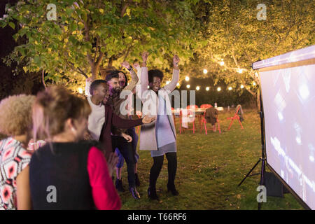 Friends cheering, watching basketball on projection screen in backyard - Stock Image
