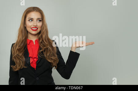 Business woman showing empty open hand on white background. Woman smiling, business and education concept - Stock Image