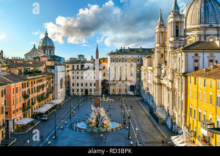 View from a window overlooking the Piazza Navona early morning, showing the cathedral, sidewalk cafes, tourists and the fountain of the Four Rivers. - Stock Image