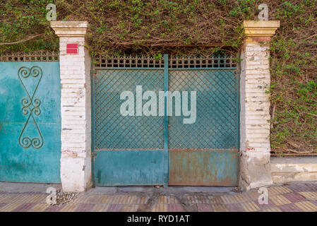 Background of green old weathered grunge antique wrought iron gate with geometrical pattern ornaments between two white bricks columns - Stock Image