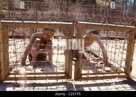 Model of two prisoners of war trapped being tortured in barbed wire cages at Phu Quoc prison, Phu Quoc, Vietnam - Stock Image