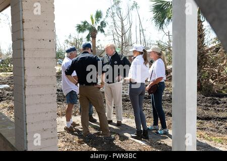 Panama City, Florida, USA. 15th Oct 2018. U.S President Donald Trump speaks to a resident during a tour of damage in the aftermath of Hurricane Michael October 15, 2018 in Lynn Haven, Florida. Standing with the president from left to right are: FEMA Administrator Brock Long, local resident, President Donald Trump, First Lady of Florida Ann Scott and First Lady Melania Trump. Credit: Planetpix/Alamy Live News - Stock Image
