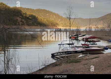 Low water level at Lake Eildon, Australia,  empty boats on the shore at sunset. - Stock Image