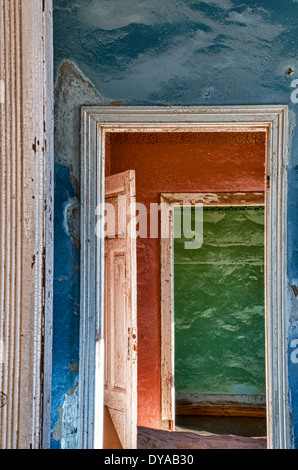 Colorful walls and open doorways to rooms full of sand in Kolmanskop, a ghost mining town in Namibia, Africa. - Stock Image