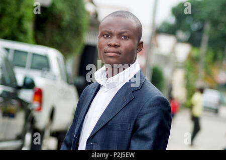 Young man in a suit standing on the street looking at the camera - Stock Image