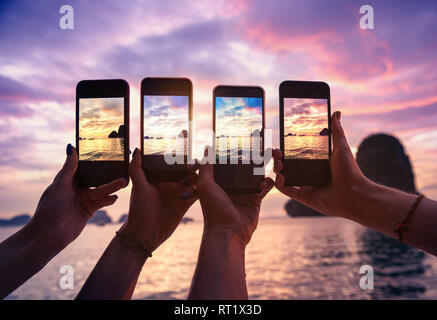 Closeup photo of four hands with mobile phones taking photo of beautiful sunset over sea bay - Stock Image