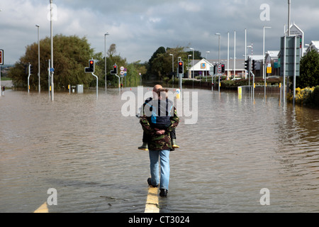 A man carries his son and walks through the flooded roads of Weymouth after torrential rain in Dorset - Stock Image
