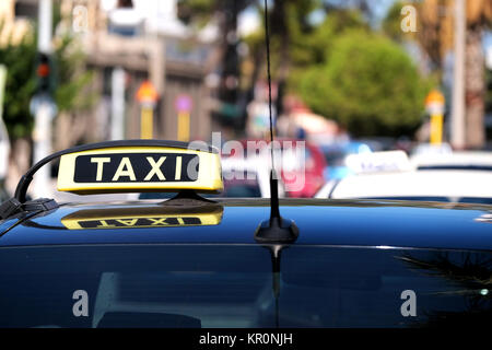 A close up of a taxi for hire sign on top of a cab. It's waiting on a taxi rank on a busy street to be hired - Stock Image
