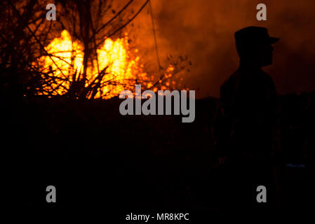 A member of the Hawaii National Guard is silhouetted by a molten lava fountain spewing liquid magma hundreds of feet into the air at the Leilani Estates residential area from the eruption of the Kilauea volcano May 23, 2018 in Pahoa, Hawaii. - Stock Image