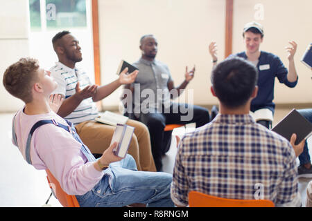 Men with bibles praying with arms outstretched in prayer group - Stock Image