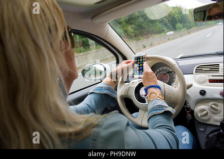 BOTTROP, GERMANY - AUG 16, 2018: A blond woman is checking her smartphone while she is driving on a highway in full speed. - Stock Image