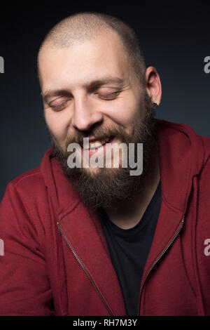 Man with beard laughing with eyes closed - Stock Image