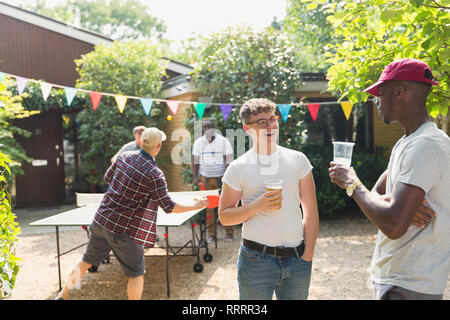 Male friends drinking beer and playing ping pong in summer backyard - Stock Image