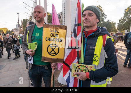 London, UK. 31st October 2018. People  in Parliament Square at the end of the Extinction Rebellion 'Declaration of Rebellion' against the British Government for its criminal inaction in the face of climate change catastrophe and ecological collapse. One holds a placard 'Save Our Children'. Peter Marshall/Alamy Live News - Stock Image