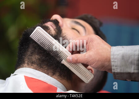 Barber making beard hairstyle using comb at barber shop . - Stock Image