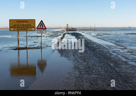 Tidal causeway road to Holy Island and Lindisfarne in  Northumberland , England, UK - Stock Image
