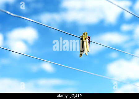 Three brightly colored plastic clothes pegs on a  family washing line with blue sky and white summer clouds in the - Stock Image