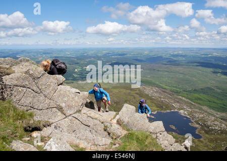 Three hikers scrambling up rocks on Carnedd Moel Siabod Daear Ddu east ridge with view down to Llyn y Foel Snowdonia - Stock Image