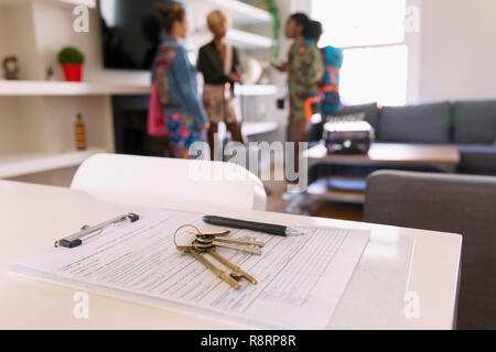 House keys and contract on table in house rental - Stock Image
