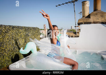Portrait playful, confident young woman sitting on inflatable pegasus in sunny rooftop hot tub - Stock Image